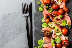 Salada com o serrano do jamon do presunto, tomates de cereja, rúcula, placa da ardósia Imagens de Stock Royalty Free