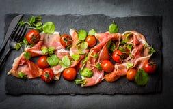Salada com o serrano do jamon do presunto, tomates de cereja, rúcula, placa da ardósia Imagem de Stock