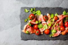 Salada com o serrano do jamon do presunto, tomates de cereja, rúcula, placa da ardósia fotos de stock royalty free