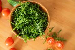 Salada com os tomates do rugula e de cereja na tabela de madeira Imagens de Stock