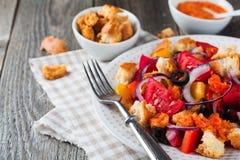 Salada com pimentas, tomates, cebolas, azeitonas e pão torrado com fundo de madeira velho do sousomna Imagem de Stock