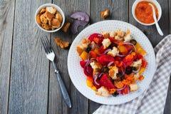 Salada com pimentas, tomates, cebolas, azeitonas e pão torrado com fundo de madeira velho do sousomna Imagens de Stock