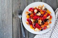 Salada com pimentas, tomates, cebolas, azeitonas e pão torrado com fundo de madeira velho do sousomna Fotos de Stock Royalty Free