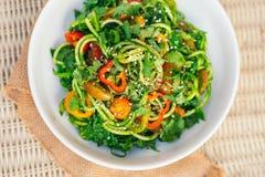 Salada com tomates amarelos, pimenta vermelha dos espaguetes do abobrinha, cebola, sementes do seasame, coentro na bacia branca S imagens de stock