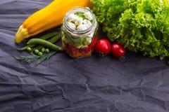 Salada com verdes no potenciômetro em uma placa de madeira, fundo textured preto do legume fresco Com espaço para o texto foto de stock
