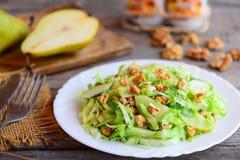 Salada da couve e da pera Salada fácil com pera, couve e as nozes frescas em uma placa branca e no fundo de madeira rústico imagem de stock royalty free
