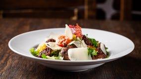 A salada da mistura de alface, de alface e de iceberg sae, com a carne dos tomates de cereja, a alaranjada e grelhado na grade S  foto de stock