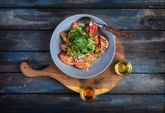 Salada da salsa da cebola dos tomates e dos dois tipos do óleo com sementes de sésamo em uma placa rústica Vista superior fotografia de stock