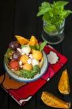 Salada das uvas melão e melancia do fruto de paixão Em um fundo preto em um guardanapo brilhante de matéria têxtil Hortelã fresca imagens de stock
