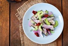 Salada de arenques com tomates sol-secados, aipo e a cebola vermelha Foto de Stock