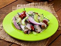 Salada de arenques com tomates sol-secados, aipo e a cebola vermelha Imagens de Stock