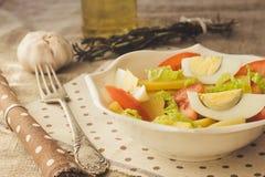 A salada de batata com ovo e tomate e o metal velho bifurcam-se Fotografia de Stock