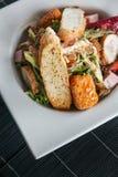 Salada de Caesar com pão torrado, o baguette cortado, os tomates de cereja e a galinha fritada na placa branca na esteira de bamb fotos de stock royalty free