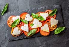 Salada de Caprese com tomates, corações do queijo, manjericão Menu do dia de são valentim Fotografia de Stock Royalty Free