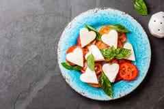 Salada de Caprese com tomates, corações do queijo, manjericão Menu do dia de são valentim Imagem de Stock