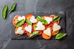 Salada de Caprese com tomates, corações do queijo, manjericão Menu do dia de são valentim Foto de Stock