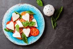 Salada de Caprese com tomates, corações do queijo, manjericão Menu do dia de são valentim Fotografia de Stock