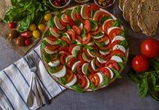 Salada de Caprese - fez da mussarela fresca cortada, tomates, folhas do basílico, com azeitonas, as forquilhas balsâmicas do vina fotografia de stock royalty free