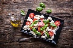 Salada de Caprese Salada mediterrânea Manjericão e azeite dos tomates de cereja da mussarela na tabela de carvalho velha Culinári imagens de stock royalty free