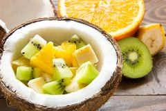 A salada de fruto é dobrada na metade de um coco em uma tabela de madeira imagens de stock royalty free