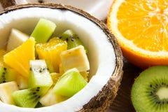 Salada de fruto com laranja e banana do quivi ao meio de um coco maduro fotos de stock