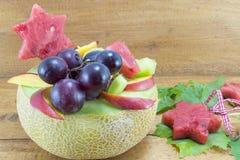 A salada de fruto original saudável serviu em um melão fresco em uma tabela de madeira Fotos de Stock