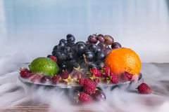 Salada de frutos deliciosa na placa na tabela, cal, framboesa, uvas imagem de stock