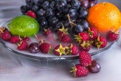 Salada de frutos deliciosa na placa na tabela, cal, framboesa, uvas imagens de stock royalty free
