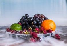 Salada de frutos deliciosa na placa na tabela, cal, framboesa, uvas foto de stock