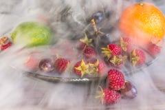 Salada de frutos deliciosa na placa na tabela, cal, framboesa, uvas fotografia de stock royalty free