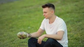 Salada de mistura do homem que senta-se na grama filme