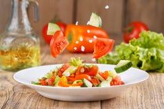 Salada do ar claro do verão de legumes frescos em um fundo de madeira Levitando ingredientes da salada Ainda vida em um estilo rú Foto de Stock