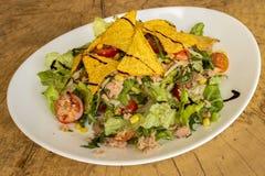 Salada do atum em uma placa branca em um fundo de madeira fotografia de stock royalty free