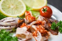 Salada do calamar com as ervas picantes do molho de pimentões e fatia grelhada especiarias do calamar na placa no restaurante do  foto de stock