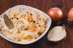 Salada do chucrute e das cenouras com folhas do louro, pimenta preta e cominhos em uma placa branca e em diversos bulbos da cebol imagens de stock royalty free