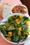 Salada do espinafre com Pecans, pêssegos e pão fresco Fotos de Stock Royalty Free