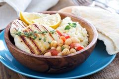 Salada do grão-de-bico, cuscuz e queijo grelhado imagem de stock
