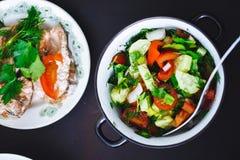 Salada do legume fresco na placa e nos peixes no fundo preto, fim acima, vista superior Alimento saudável, almoço imagem de stock royalty free