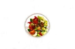 Salada do pepino dos tomates de cereja dos legumes frescos saboroso em uma opinião superior da bacia transparente e em um branco Imagens de Stock Royalty Free