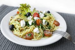 Salada do pepino do tomate e de peixes vermelhos e fatias de queijo em uma placa Iaelate em um fundo branco fotos de stock royalty free