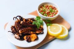 Salada do polvo com ervas e especiarias do limão na placa branca - o calamar dos tentáculos grelhou o molho quente e picante do a imagens de stock