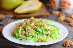 Salada do slaw da couve da pera Salada caseiro com pera, couve e as nozes frescas em uma placa branca e no fundo de madeira rústi fotos de stock royalty free