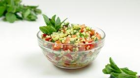 Salada do taboulé em uma bacia de vidro em um fundo branco fotos de stock