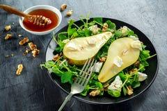 Salada doce fresca das peras com nozes, mel e queijo macio branco na placa preta fotografia de stock royalty free
