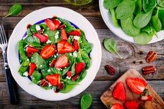 Salada dos espinafres com as porcas das morangos, de queijo de feta, as balsâmicas e de noz-pecã fotos de stock