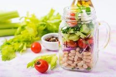 Salada dos feijões brancos, do tomate, do aipo, do pepino, da rúcula, da cebola vermelha e do queijo de feta em um frasco Fotografia de Stock Royalty Free