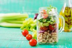 Salada dos feijões brancos, do tomate, do aipo, do pepino, da rúcula, da cebola vermelha e do queijo de feta em um frasco Foto de Stock