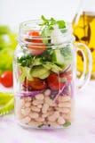 Salada dos feijões brancos, do tomate, do aipo, do pepino, da rúcula, da cebola vermelha e do queijo de feta em um frasco Fotos de Stock