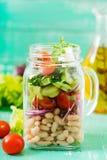 Salada dos feijões brancos, do tomate, do aipo, do pepino, da rúcula, da cebola vermelha e do queijo de feta em um frasco Imagem de Stock Royalty Free