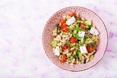 Salada dos feijões brancos, do tomate, do aipo, do pepino, da rúcula, da cebola vermelha e do queijo de feta na bacia Fotografia de Stock